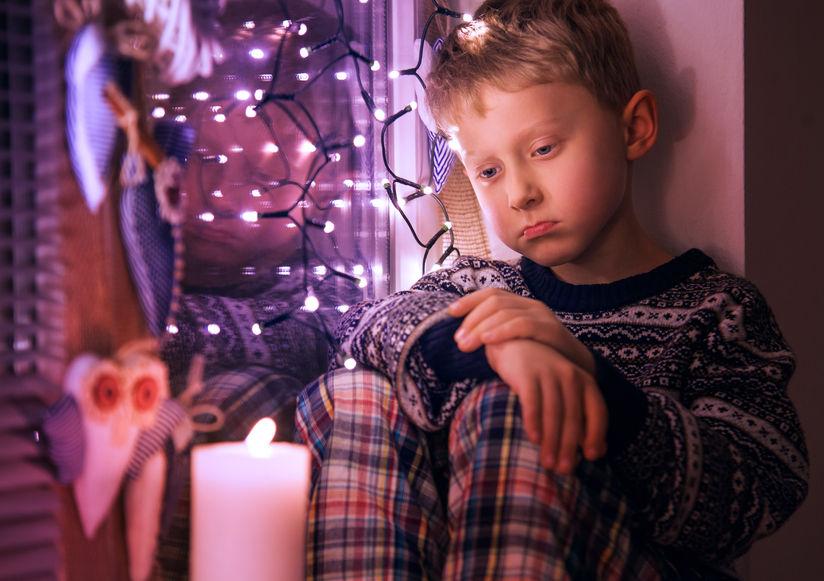 Un niño triste espera los regalos en Navidad